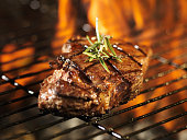 steak with flames on grill with rosemary