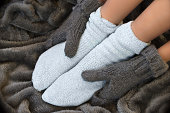 Feet in comfortable and warm woolen stocks on a blanket