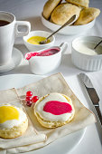 Scones with whipped cream, lemon curd and cranberry jam