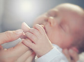Newborn is Holding fathers Hand