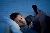 man in couch falling asleep using mobile phone