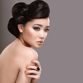 Beautiful girl with oriental type evening hair and makeup.