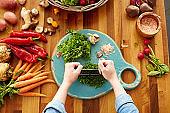 Woman cutting cilantro with mezzaluna knife