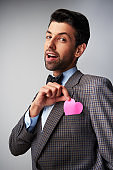Casual man hiding pink heart shaped sticker at pocket