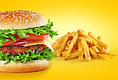 Hamburger with fries on a yellow background.