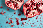 High angle close-up of pomegranate on messy cutting board