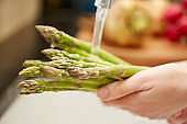 Close-up of female hands washing asparagus under water
