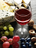 Types of cheeses with wine glass and fruits.