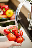 Close-up of hands holding tomatoes under faucet