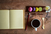 Colorful macaroons and a cup of coffee with blank notebook