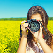 Portrait of a young woman with a camera outdoors