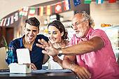 Senior man using digital tablet with teenage couple