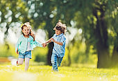 Happy kids having fun outdoors while holding hands and running.