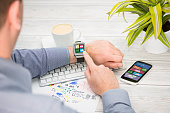 Businessman uses smart watch and phone.