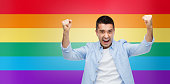 angry man with raised hands over rainbow flag