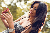 Smiling woman text messaging on smart phone outdoors.