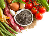 Raw chia seeds in bowl and vegetables