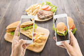 Friends using smartphones to take photos hot dog and hamburger