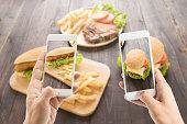 Friends using smartphones to take photos hot dog and hamburger