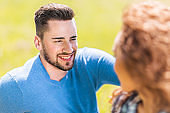 Young smiling man in love communicating with his girlfriend outdoors.