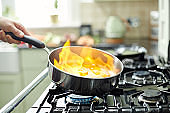 Flambé flames rising in frying pan with mushrooms