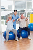Senior couple on exercis ball with trainer