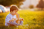 Cute boy, playing with airplane on sunset in the park
