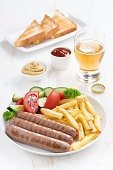 grilled sausages with French fries, vegetables and glass of beer