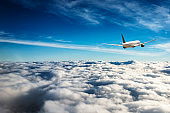commercial airplane flying on the clouds