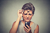 young woman with glasses having trouble seeing cell phone