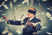 Blindfolded senior businessman trying to catch dollar bills banknotes