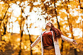 Carefree young woman having fun in autumn day outdoors.