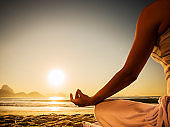 Unrecognizable person meditating on the beach at sunset.