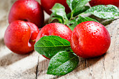 Ripe red plums on old wooden background