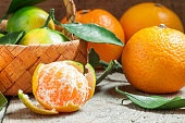 Ripe peeled tangerines with green leaves