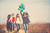Friends running with balloons, carefree, fun, enjoyment