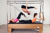 Pilates aerobic instructor a group of three people in cadillac