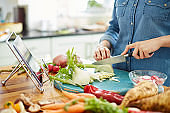 Woman chopping fennel bulb on table in kitchen