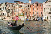 Venetian gondolas with tourists sail in the canal in Venice
