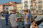 Gondoliers are waiting for tourists on the canal, Venice, Italy