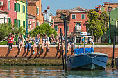 Teenagers sit by the Burano canal , Italy