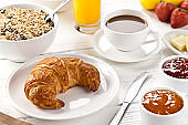 Freshly baked croissant served on a withe rustic dinning table.