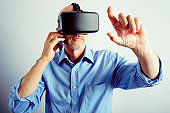 Professional Man Using Virtual Reality Headset And Mobile Phone