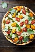 Cherry tomato pizza with mozzarella and basil pesto