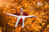 Carefree couple enjoying in autumn day at the park.