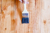 Brushing to apply varnish paint on a wooden surface