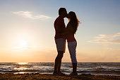 Couple Kissing At Beach During Sunset