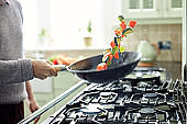 Man tossing fresh vegetables in saucepan at kitchen