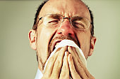 Aaachoo! Red-nosed man suffering from a cold sneezes into handkerchief