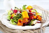 Salad with slices of pumpkin on a plate